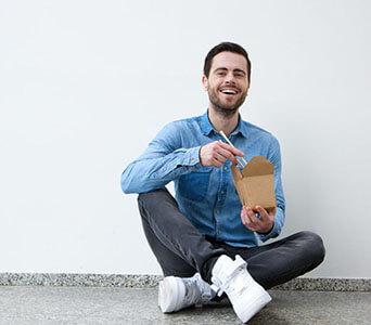 young-man-enjoying-chinese-food
